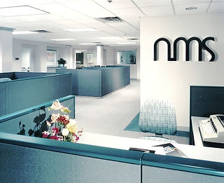Commercial Interior Design, office interior, glass walls, wood trim, gray commercial carpet, gray cubicles, gray and teal colorway, wall signage, reception desk, short cubicals,