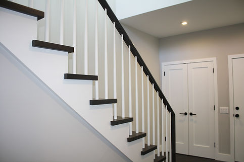 transitional stairs, white balusters, dark wood handrail, dark wood treads, beige paint, beige walls, white doors, dark wood floor