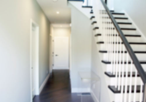 entry montauk condominium, stairway design montauk, gray walls, black handrail, dark wood floor, white balusters