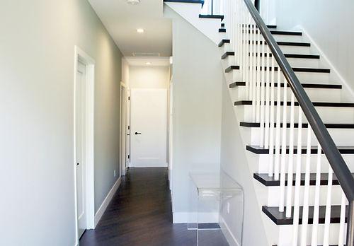 entry montauk condominium, stairway design montauk, gray walls, black handrail, dark wood floor, white balusters