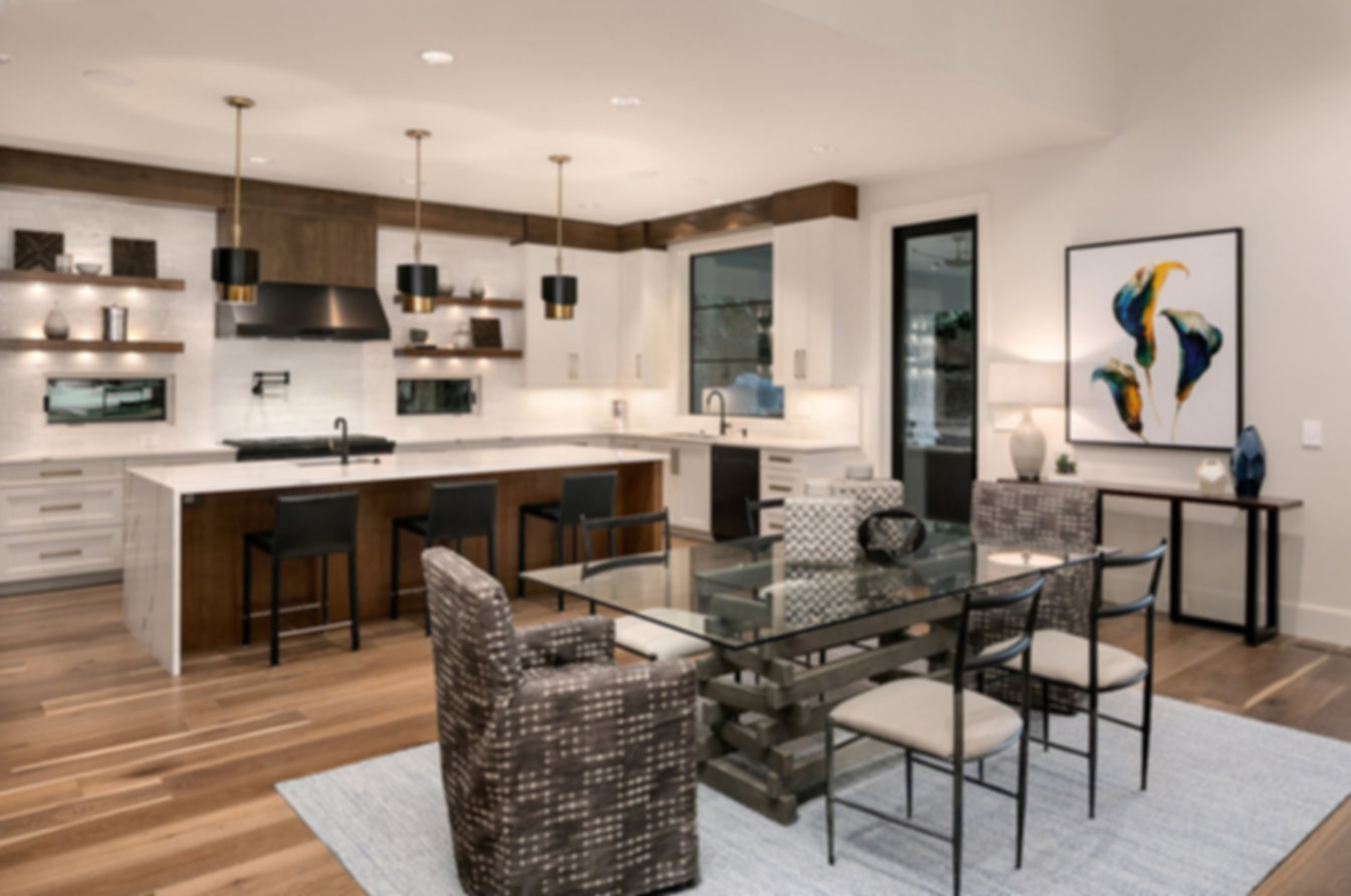 Hamptons kitchen, wood cabinets, copper hood, waterfall marble top, open shelving, glass and steel dining table, slipcovered dining chairs, white and steel dining chais, black leather bar stools with backs.