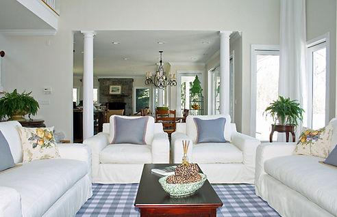 white couches, blue and white room, plaid rug, throw pillows, white drapery,