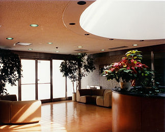 Commercial interior, wood Reception desk, commercial interior design, round reception desk, metal stairway railing, ceramic tile floor, overhead lighting, curved couches.