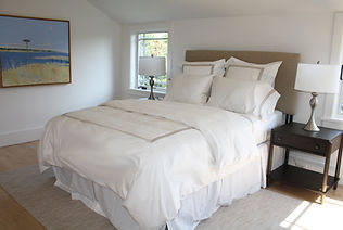 Sag Harbor bedroom design, upholstered headboard, white bed linens, gray rug,