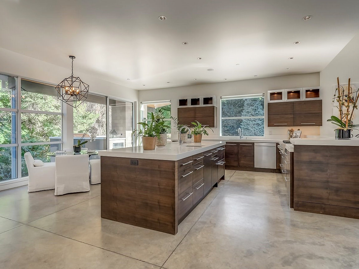 wood kitchen cabinets, white quartz countertop, poured cement floor, white upholstered dining chairs, glass breakfast table