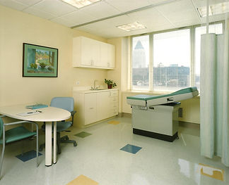 Medical Office Design,  Exam Room design, green blue ad yellow, patterned vinyl floor, cubicle curtains, medicl cabinetry, exam table, natural light
