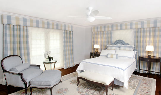 traditional bedroom design, plaid fabric, blue and white, blue headboard, upholstered headboard, blue slipper chair, blue fabric chair, oriental rug, dark wood floors, dark wood nightstands, white bench, upholstered bench, wallcovering