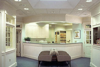 Medical office design Hampton medical office, white reception desk, beadboard walls, lighting soffit, wallpaper, reception chairs, blue and beige office design, fish tank, upholsterd waiting room chairs