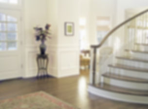 East Hampton traditional interior design, hamptons traditional interior design, dark wood floors, curved staircase, wood bannister, paneled walls, oriental rug, post modern interior design in the hamptons
