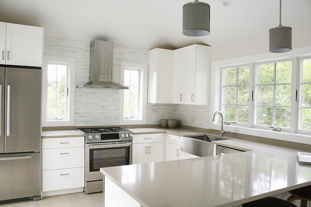 Contemporary Hamptons Kitchen, white modern kitchen, white shaker cabinets, farm sink, stainless farm sink, kitchen with peninsula, brown countertop, gray pendant fixtures, tile backplash, kitchen windows