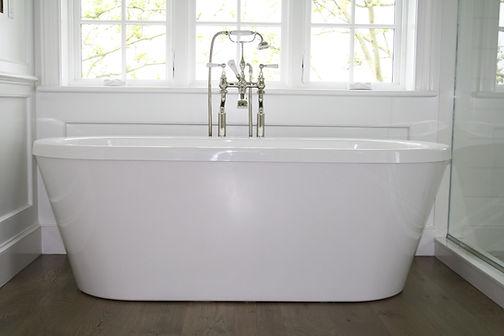 Traditional bathroom, white bathtub,  freestanding bathtub, wood bathroom floors, tub filler,