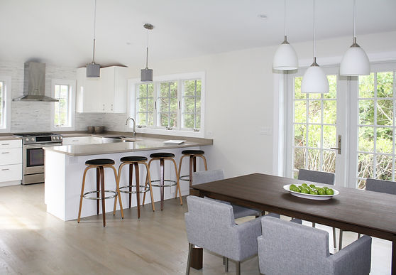 wood dining table, white kitchen cabinets, taupe quartz countertops, wood barstools, gray modern dining chirs, white pendant fixtues, stainless appliances, gray wood floors