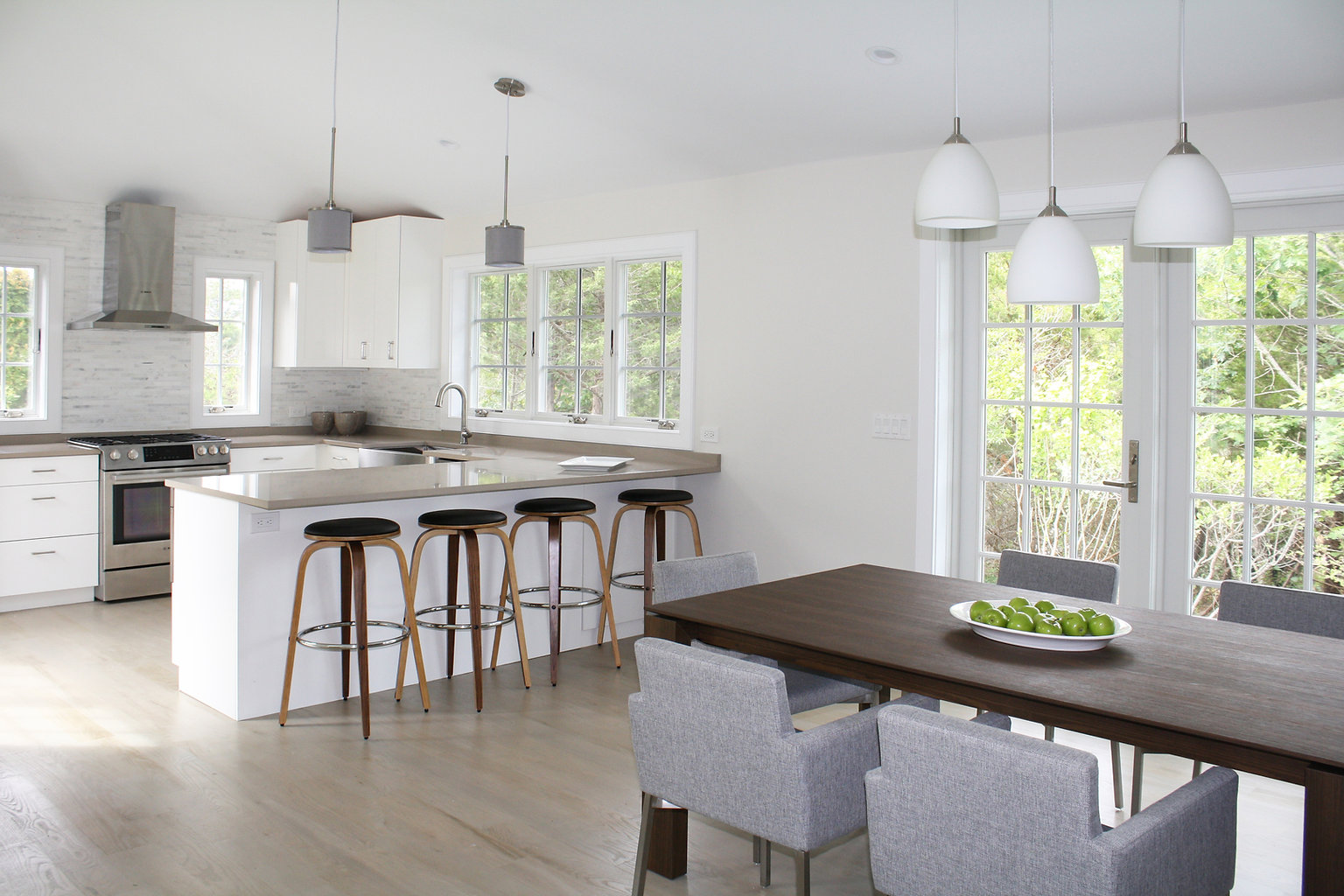 Contemporary Hamptons Kitchen, tile backsplash, white cabinets, stainless farm sink, stainless steel appliances and hood, wood bar stools, modern wood dining table, gray dining chairs, modern dinin chairs, white pendant fixture, gray pendant lighting, gray wood floor