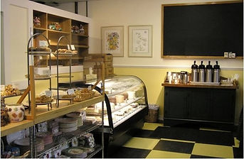 Retail Design, Bakery interior, glass display case, coffee station, checkered floor, yellow and black, East Hampton Store Design