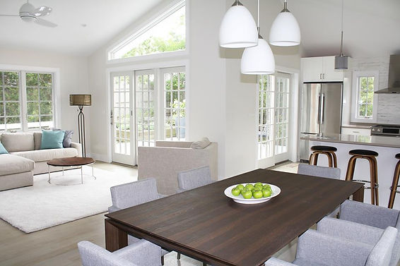 modern interior, modern design, midcentury modern, pendant lamps, wood diming table, modern dining table, gray dining chairs, gray modern dining chairs, white shag rug, beige couch gray stained floors, wood stools, transom window