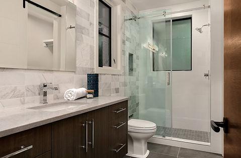 wood vanity, white quartz top, white toilet, frameless shower doors, black hardware, black tile floors,
