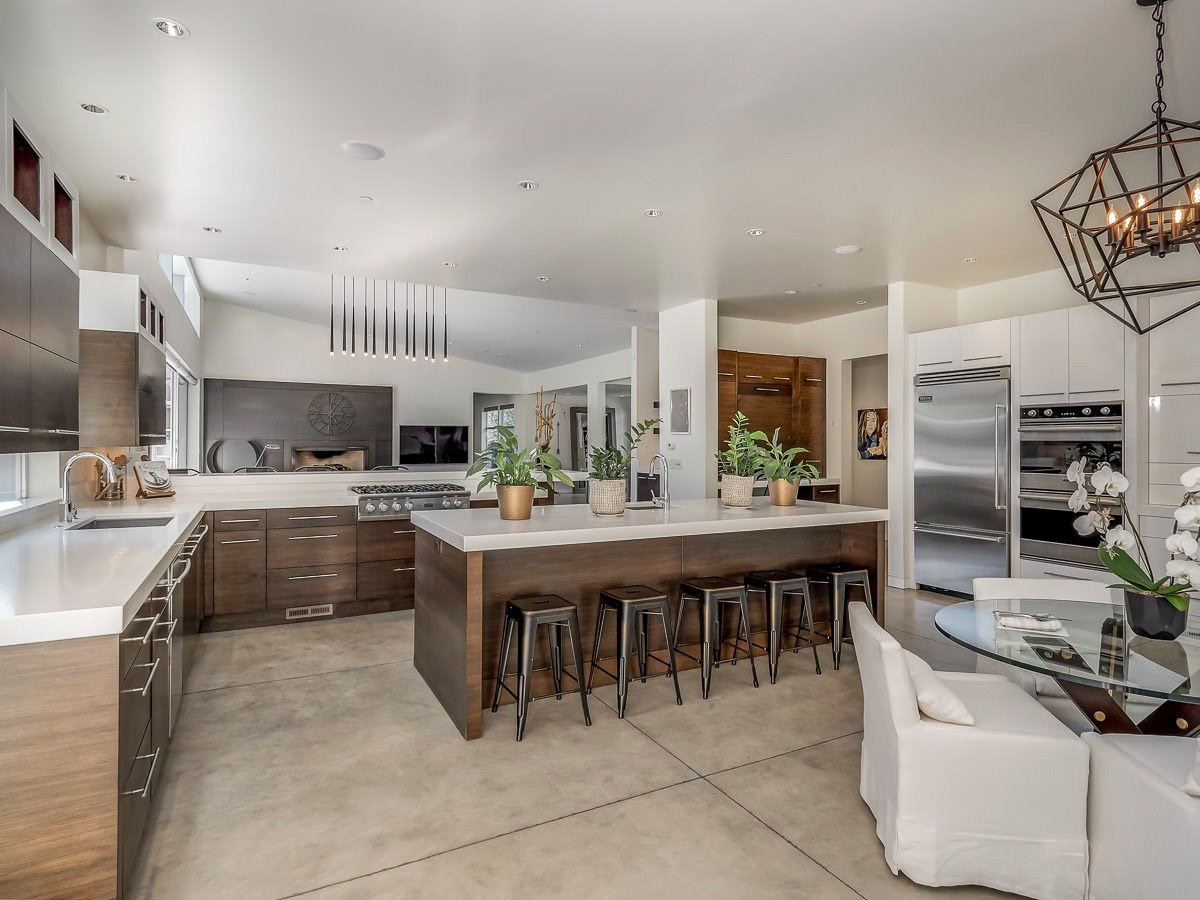 wood kitchen cabinets, white quartz countertop, poured cement floor, white upholstered dining chairs, glass breakfast table, metal bar stools, modern pendant