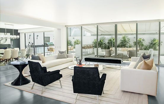 living room design, black side chairs, white sofas, glass coffee table, white and gray rug, dark gray wood foors, glass wall, dining table, upholstered dinng chairs, outside eating area, outside cooking