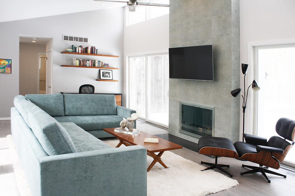 Blue sectional, Black leather chair, midcentury modern, eames chair, white shag rug, stone fireplace, gray wood floors