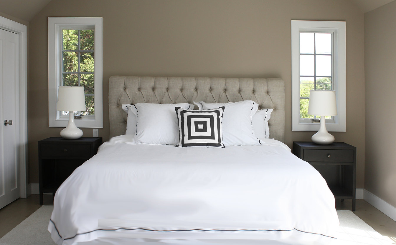 master bedroom design, upholstered headboard, tufted headboard, linen headboard, casement windows. whice lamps, modern lamps, dark wall paint, brown wall pait, modern nightstands, white shag rug, throw pillow, white linens