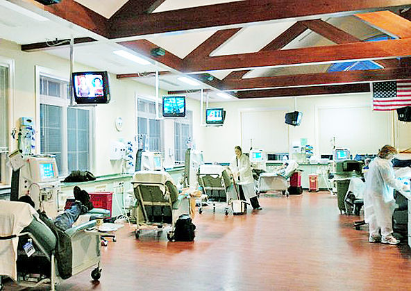 Dialysis Treatment room, wood trusses, teal treatment chairs, wood floor, medical cabinetry, overhead televisions,