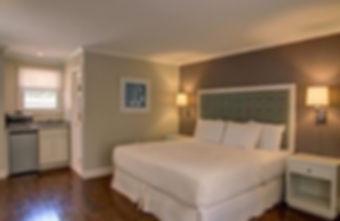 Hospitality Design, Hamptons motel design, accent wall, upholstered h Motel renovation upholstered headboard, white motel furniture, white linens, wood floors, hotel lighting, sconces, tan and blue hotel design