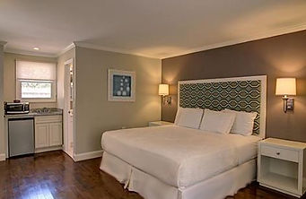 Hospitality Design, Hamptons motel design, accent wall, upholstered h Motel renovation upholstered headboard, white motel furniture, white linens, wood floors, hotel lighting, sconces, tan and blue hotel design