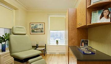 Medical Office Design, wood cabinetry, green and beige, light wood floors, artworkcustom cherry desk area, ivory exam chair