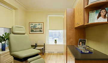 Medical Office Design, wood cabinetry, green and beige, light wood floors, artworkcustom cherry desk area, ivory exam chair