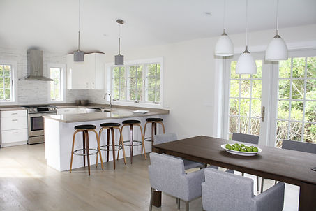 Kitchen design Amagansett with modern wood dining table, counter stools, kitchen renovation, quartz countertop, white kitchen cabinets, gray floors, modern gray dining chairs, pendant fixtures, dining chandelier, stainless steel hood, tile backsplash