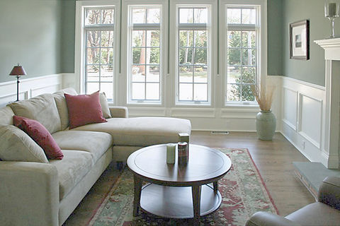 beige sectional, traditional den, round wood coffee table, oriental rug, red and green, green walls, white paneling, large windows, dark wood floor