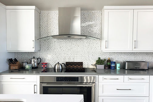 white transtional kitchen, white kitchen, stainless steel hood, tile backsplash, white backsplash, gray countertop, white kitchen cabinets, shaker cabinets