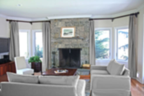 stone fireplce, gray drapery, gray couches, wood floor, wood coffee table