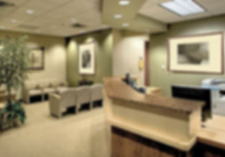 Medical Office Design, reception desk, art, granite desktop, beige seating, reception chairs, green wawood cabinetry, green and beige, light wood floors, artwork, light green walls,