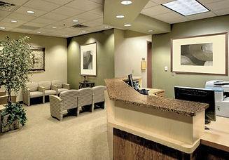 Medical Office Design, reception desk, art, granite desktop, beige seating, reception chairs, green wawood cabinetry, green and beige, light wood floors, artwork, light green walls,
