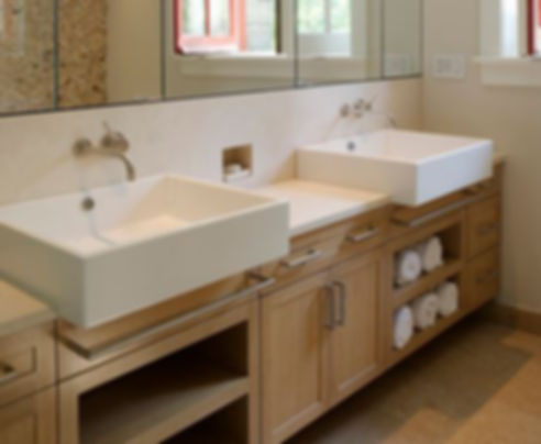 Light wood bathroom double vanity has dual white vessel sinks, and wall mounted faucets