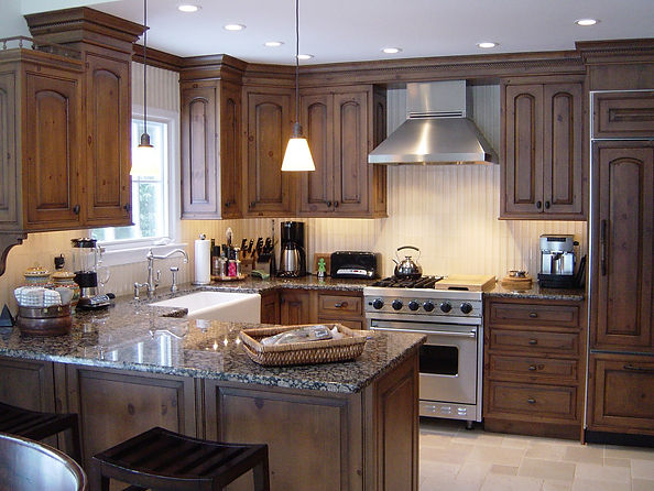 Small but complete traditional kitchen East Hampton granite countertops, farm sink, wood cabinets, tile backsplash, hood