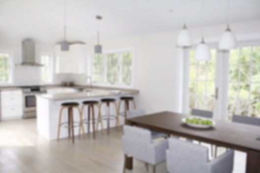 modern interior design, contemporary interior, wood dining table, modern dining table, wood barstools, modern kitchen, white cabinetry, white kitchen cabinets, stainless steel hood, gray countertops, gray wood floor, white pendant fixture, white glass lights, gray dining chairs, modern dining chairs