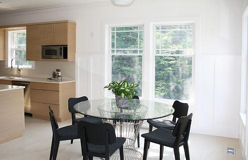 Kitchen design Amagansett, midcentury modern table, black dining chairs, globe lights, glass top table, modern cabinetry, cherry cabinetry, kitchen cabinets, limestone floor