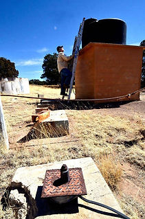 Rancher Ray Pittman checks his water tank