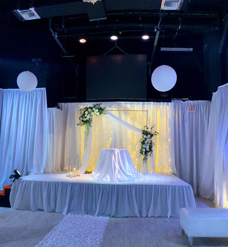 white decorated stage at wedding hall