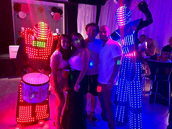 Happy people posing for a photo with two entretainers with light suits