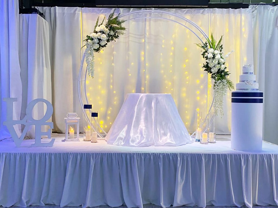 white stage decorated with flowers
