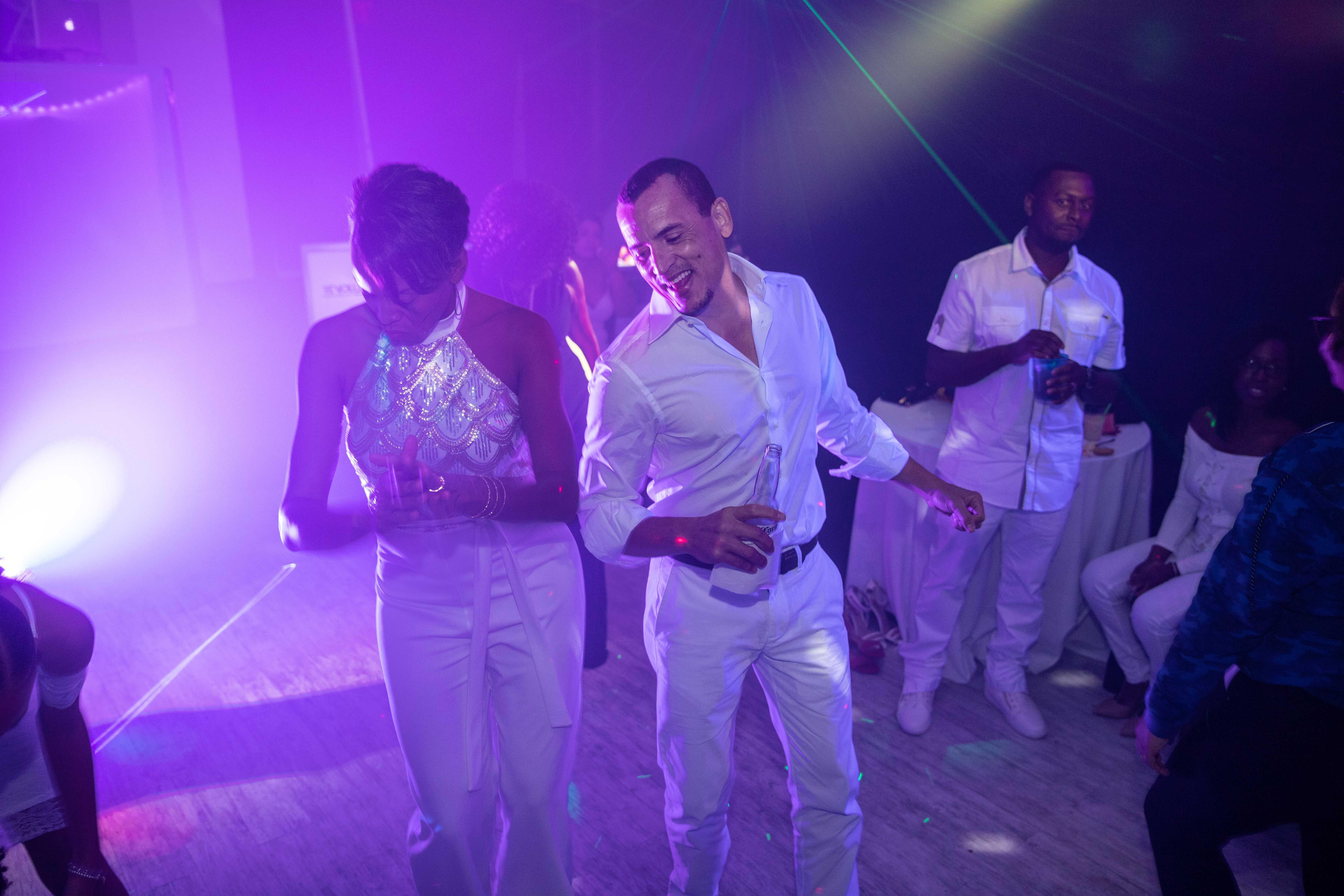 Man dancing in a partu venue with purple lights
