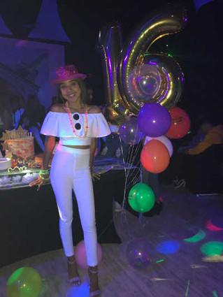 birthday girl with sweet 16 balloon arrangement