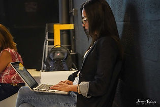 Woman writing in a laptop in a event venue