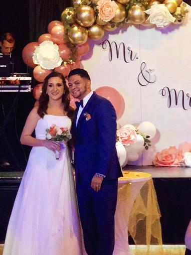Spouses in front of wedding balloons arrangement