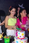 birthday girl chopping cake at teen party