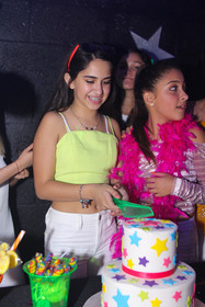birthday girl chopping cake at teen party