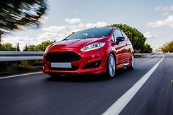 red-mini-coupe-driving-highway-with-high
